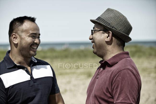 Due uomini sorridenti sulla spiaggia — Foto stock