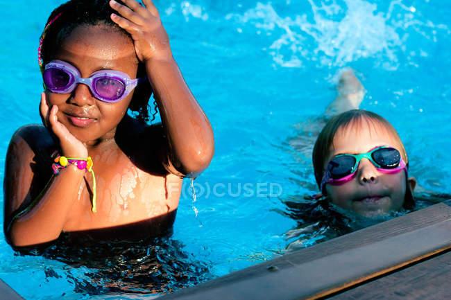 Девочки плавают в бассейне — стоковое фото