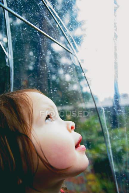 Menina inclinada para a janela e assistindo gotas de chuva — Fotografia de Stock