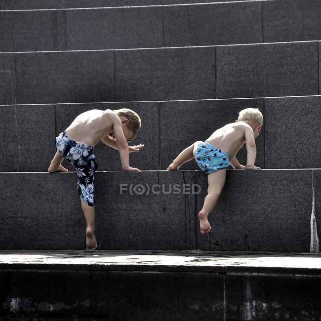 Boys climbing on steps — Stock Photo