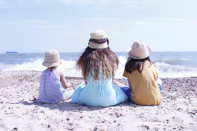 Три девушки сидят на пляже — стоковое фото