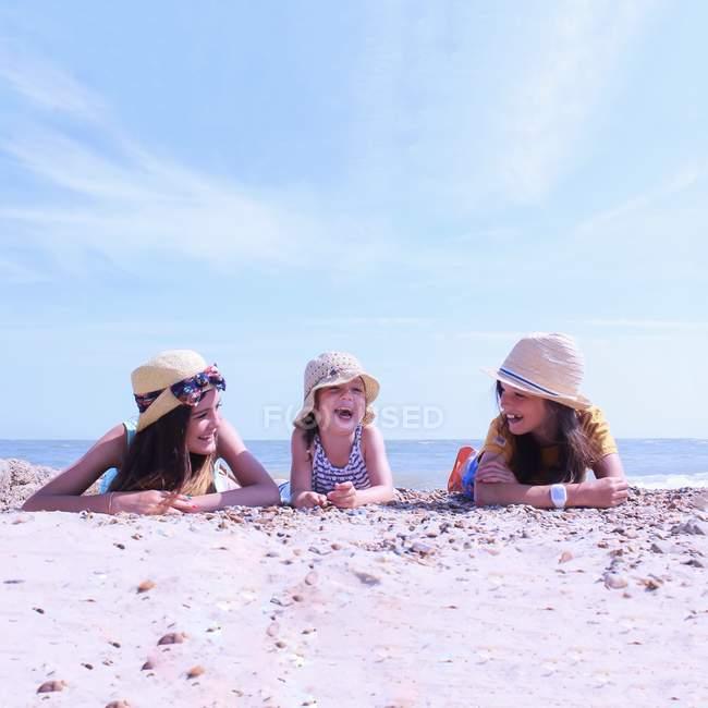 Beautiful girls lying on beach — Stock Photo