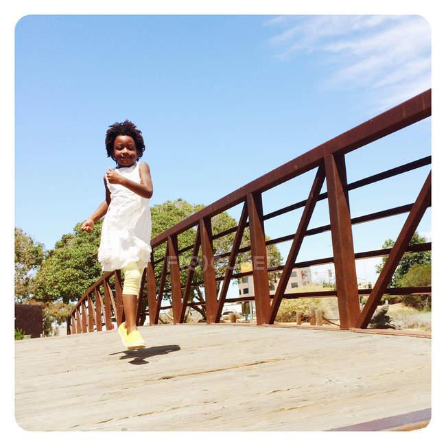 Junge Mädchen laufen auf Brücke — Stockfoto