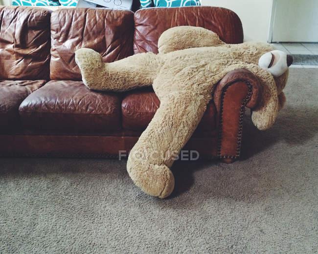 Фаршированный плюшевый мишка лежит на диване — стоковое фото