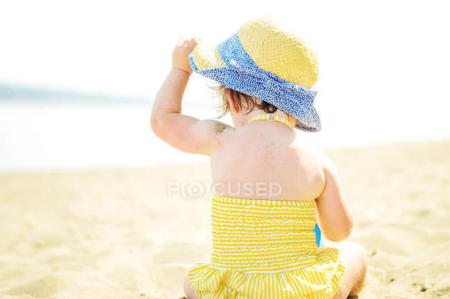 Дівчина сидить на пляжі — стокове фото