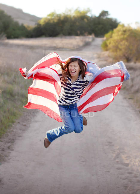 Ragazza che salta mentre tiene la bandiera americana — Foto stock