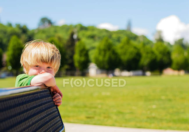 Boy leaning on bench — Stock Photo