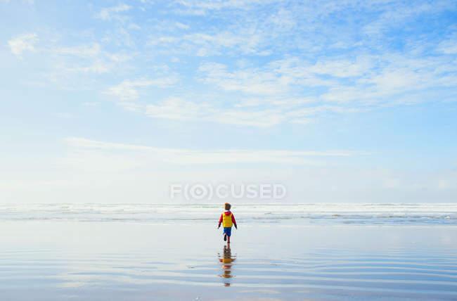 Garoto andando na praia — Fotografia de Stock