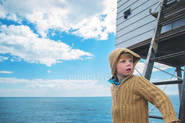Мальчик стоит на лестнице и смотрит в сторону — стоковое фото