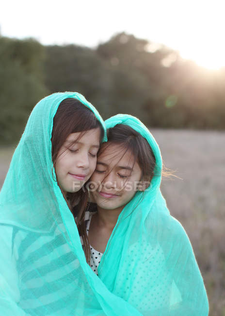 Two girls wrapped in blanket — Stock Photo