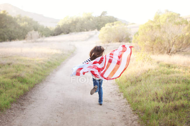 Girl running on footpath with American flag — Stock Photo