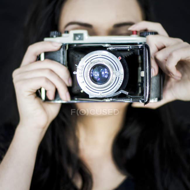 Woman with old camera against face — Stock Photo