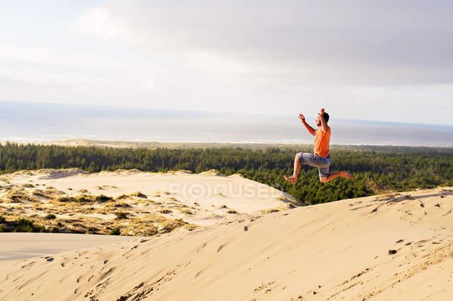 Человек прыгает на песчаных дюн — стоковое фото