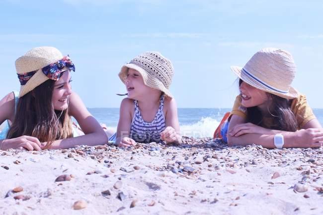 Три девушки, лежащие на пляже — стоковое фото