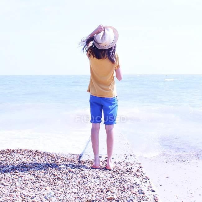 Kleines Mädchen steht am Strand — Stockfoto