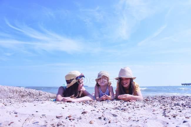 Three Girls lying on beach — Stock Photo