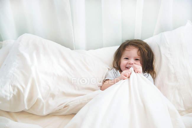 Menina de pijama deitada na cama — Fotografia de Stock