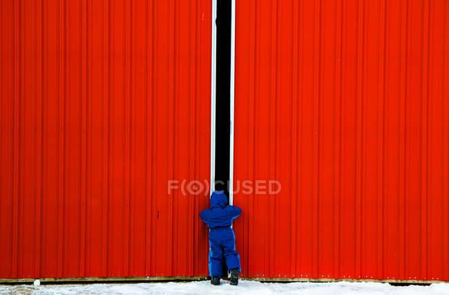 Junge schaut durch Türspalt — Stockfoto
