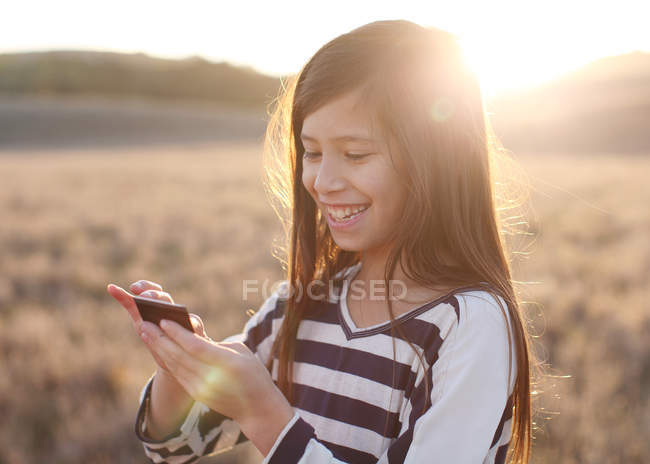 Girl standing in meadow and text messaging — Stock Photo