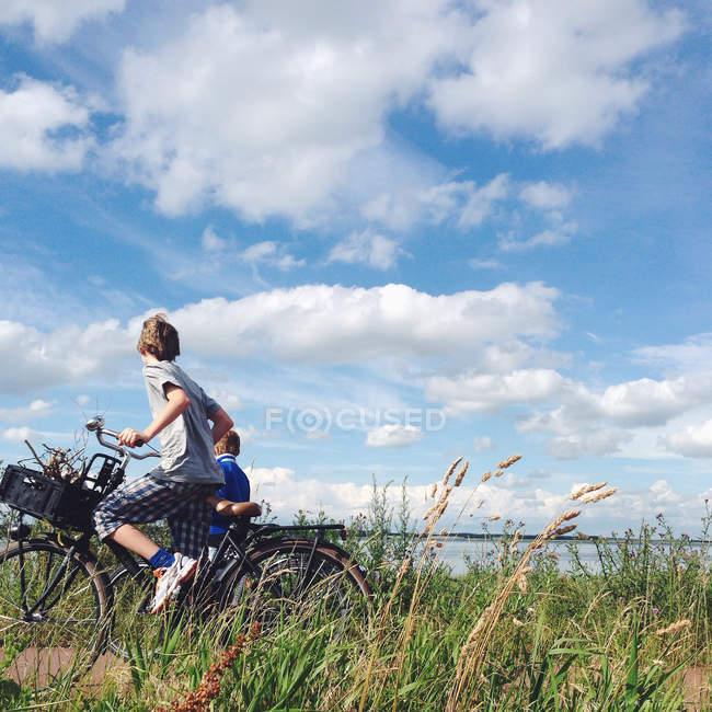 Two boys biking near sea — Stock Photo