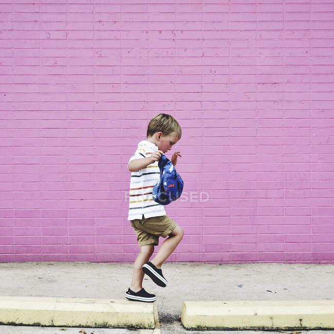 Little boy walking on sidewalk — Stock Photo