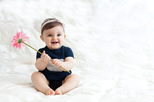 Baby girl playing with flower — Stock Photo