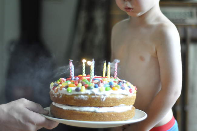 Boy blowing out candles on cake — Stock Photo