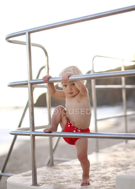 Toddler climbing on lifeguard tower railings — Stock Photo