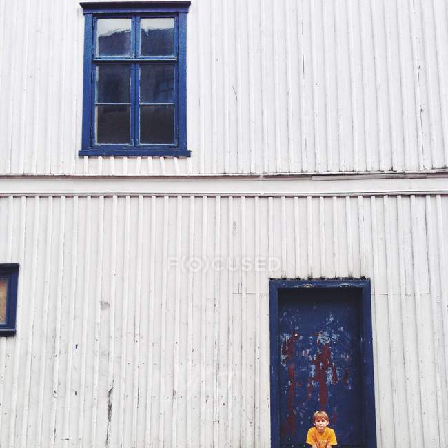 Boy sitting against house — Stock Photo