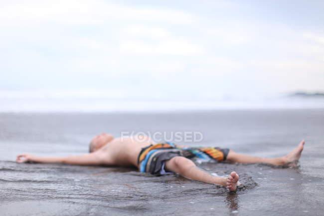 Мальчик, лежащий на пляже — стоковое фото