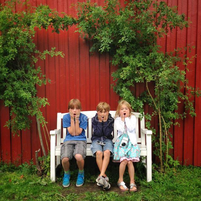 Tre bambini che si siedono sul banco — Foto stock