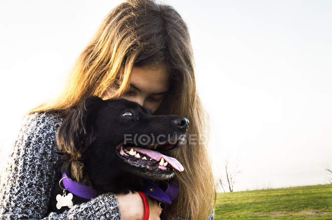 Teenage girl hugging dog — Stock Photo