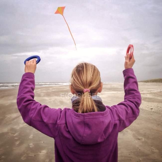 Girl flying kite on beach — Stock Photo