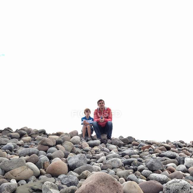 Father and son sitting on rocks — Stock Photo