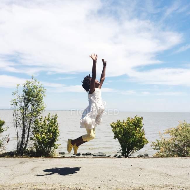 Fille sautant sur la plage — Photo de stock