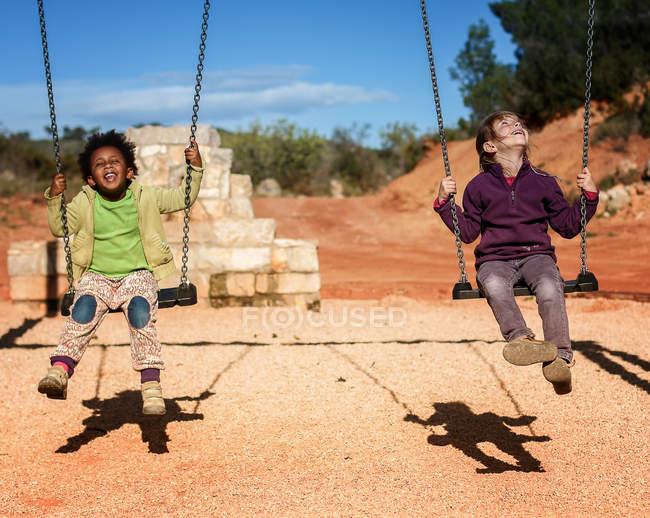 Smiling little children swinging — Stock Photo