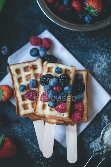 Berries and waffles on sticks — Stock Photo