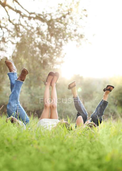 Kinder liegen auf Rasen und heben die Beine — Stockfoto