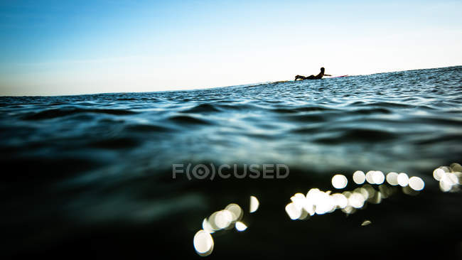 Woman in ocean paddling on surfboard — Stock Photo