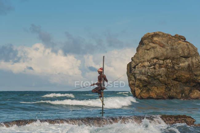 Pescador sobre pilotes de pesca - foto de stock