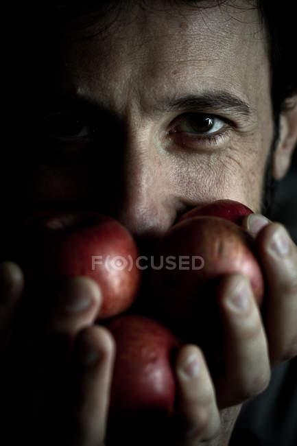 Man is holding apples in front of face — Stock Photo