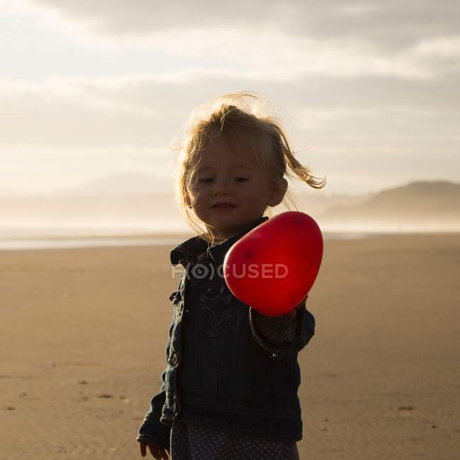 Niña sosteniendo globo rojo - foto de stock