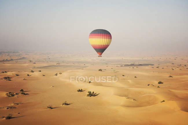 Hot air balloon over the desert — Stock Photo