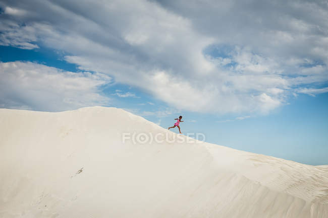 Girl running down sand dune — Stock Photo