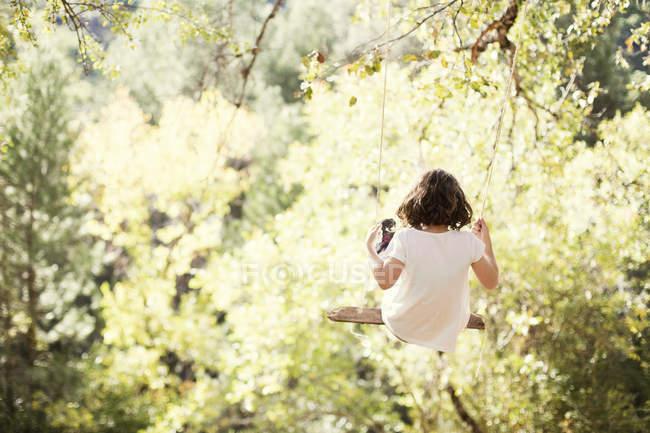 Chica sentada en swing - foto de stock