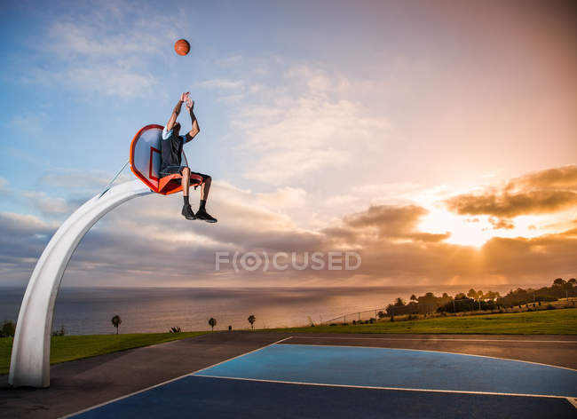 Man sitting in basketball hoop — Stock Photo