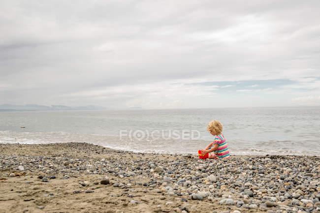 Niña jugando en la playa - foto de stock