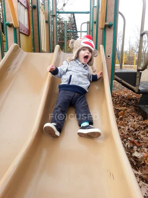 Junge rutscht auf Spielplatz — Stockfoto