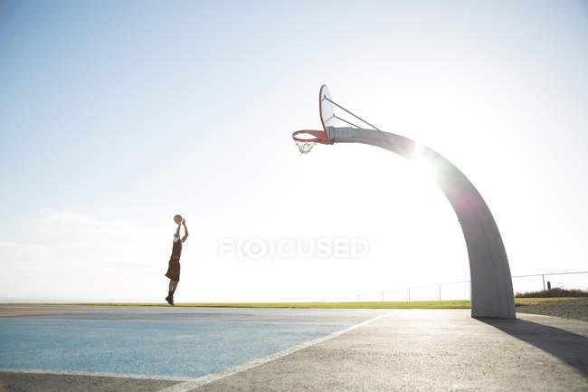 Мужчина играет в баскетбол в парке — стоковое фото