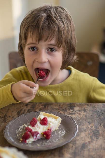 Boy eating strawberry tart — Stock Photo